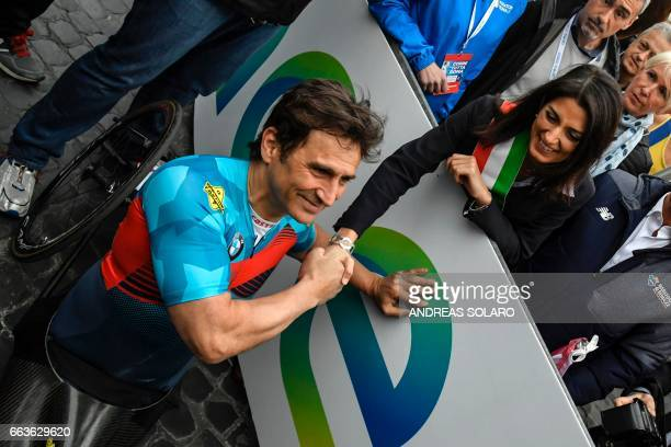 Former racing driver and paracyclist Italian Alex Zanardi shakes hands with Mayor of Rome Virginia Raggi as he takes part in the 23rd Marathon of...