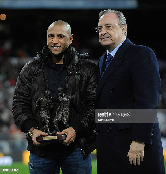 Former Real Madrid player Roberto Carlos is presented with a trophy for his achievements at the club by president Florentino Perez during the La Liga...