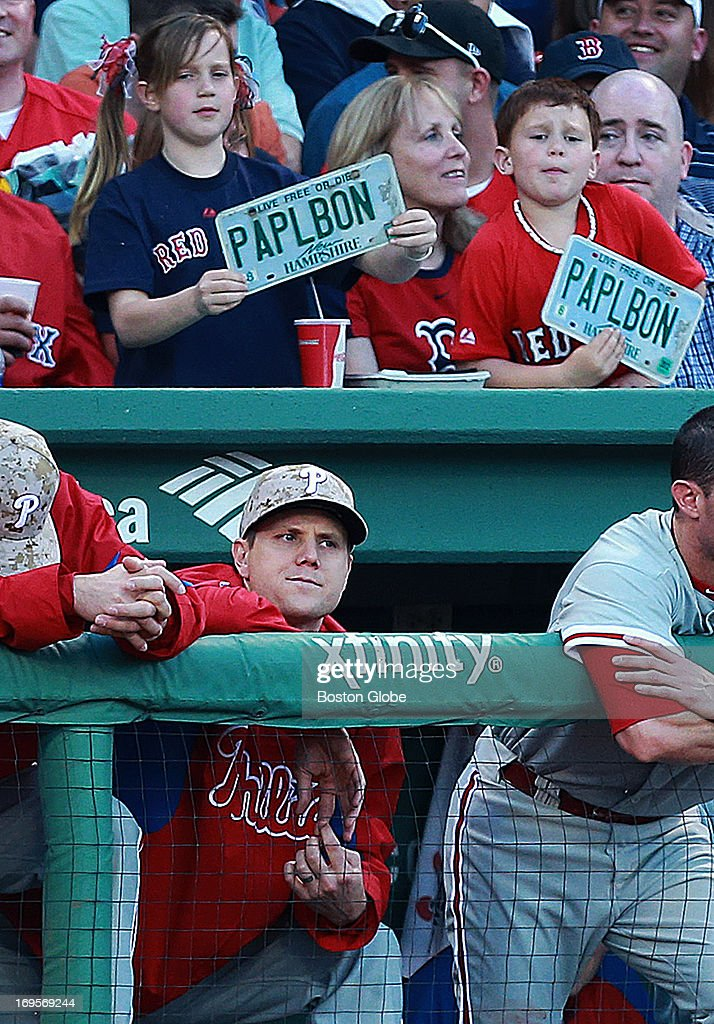 Former Red Sox closer Jonathan Papelbon makes his return to Fenway Park in a Phillies uniform tonight. He stands in the dugout after a video tribute to him was played on the scoreboard. Two fans hold New Hampshire license plates behind him in the stands. The Philadelphia Phillies visited the Boston Red Sox in a regular season MLB baseball game at Fenway Park.
