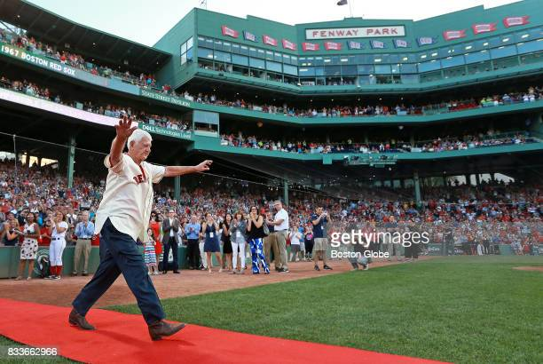 Former Red Sox player Carl Yastrzemski waves to the fans as he and other members of the 1967 'Impossible Dream' team are honored before the start of...