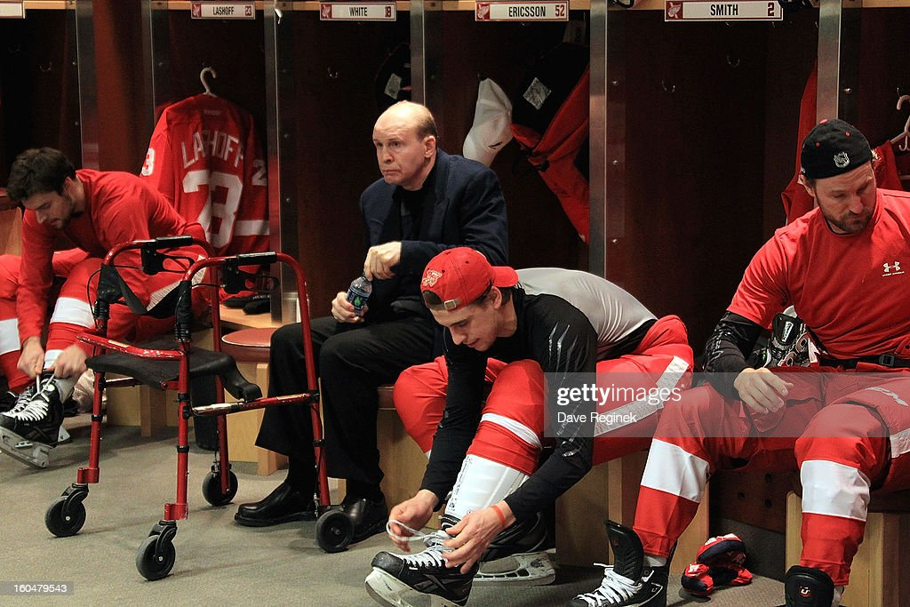 Former Red Wing Vladimir Konstantinov sits between Brendan Smith #2 and Brian Lashoff #23 of the Detroit Red Wings before an NHL game against the Dallas Stars at Joe Louis Arena on January 25, 2013 in Detroit, Michigan. Detroit won the game 5-3