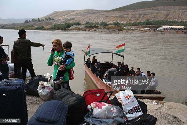 Former refugees prepare to board a ferry to cross the Tigris River from Iraq into Rojava Syria on November 8 2015 at Simalka Syria The predominantly...