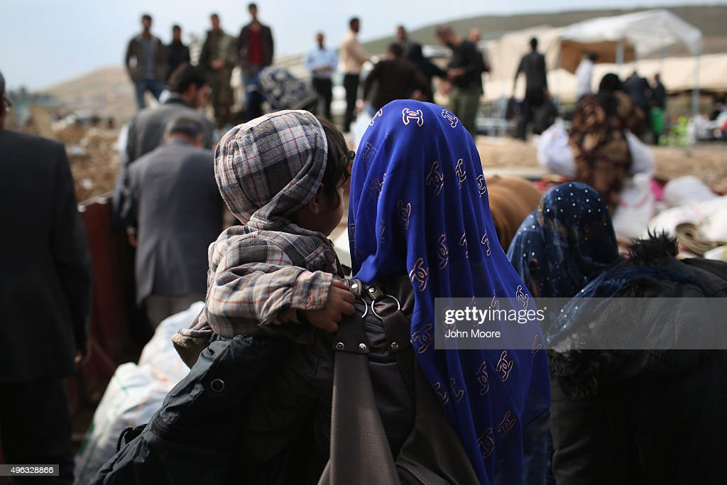 Former refugees prepare to step onto Syrian soil after crossing the Tigris River from Iraq while returning to their homeland of Rojava Syria on...