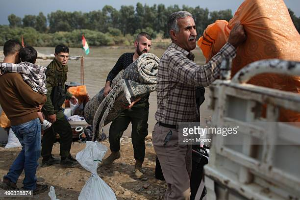 Former refugees unload new household belongings after crossing the Tigris River from Iraq while returning to their homeland of Rojava Syria on...