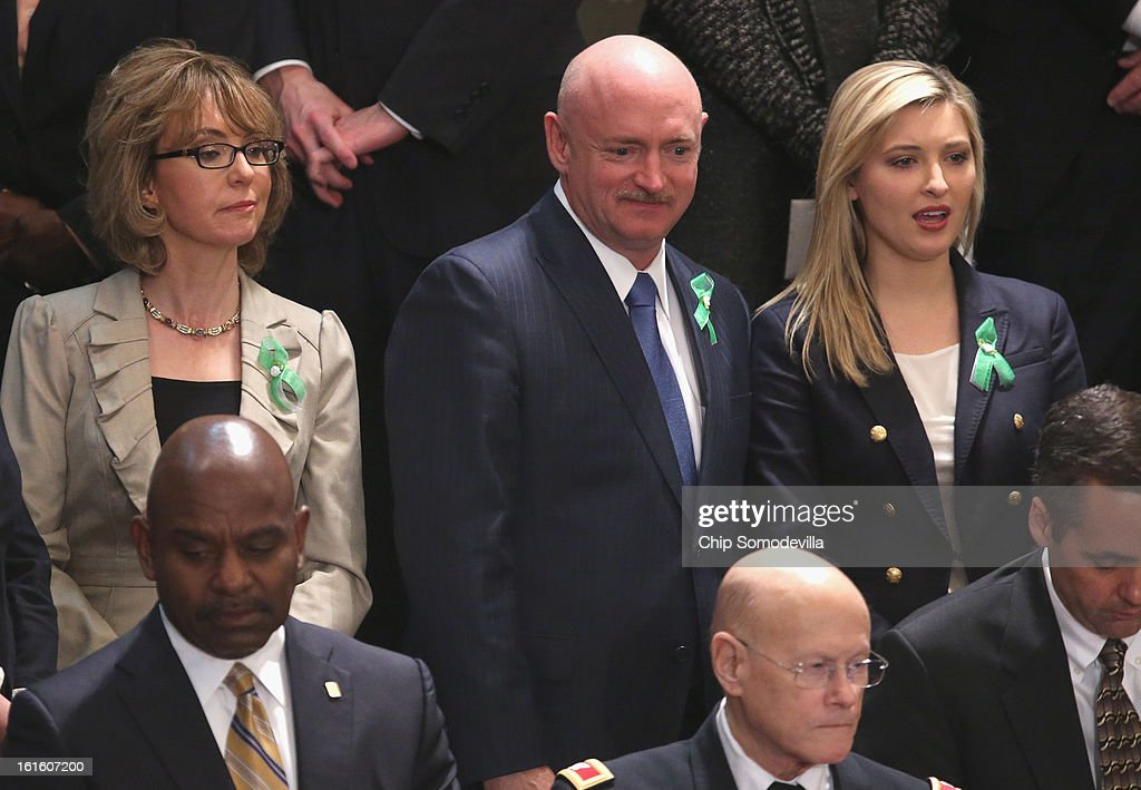 Former Rep. Gabby Giffords (L) and her husband Mark Kelly (C) listen as U.S. President Barack Obama delivers his State of the Union speech at the U.S. Capitol February 13, 2013 in Washington, DC. Facing a divided Congress, Obama concentrated his speech on new initiatives designed to stimulate the U.S. economy and said, 'It's not a bigger government we need, but a smarter government that sets priorities and invests in broad-based growth'.