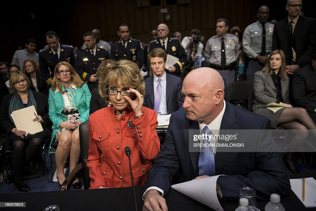 Former Rep. Gabrielle Giffords, and her husband retired Astronaut Mark Kelly, take their seats during a hearing of the Senate Judiciary Committee on Capitol Hill January 30, 2013 in Washington, DC. The committee held the hearing with Mark Kelly, Wayne LaPierre, Chief Executive Officer of the National Rifle Association, and others to testify about solutions to gun violence in the United States. AFP PHOTO/Brendan SMIALOWSKI