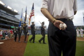 Former Rep Zack Wamp watches the US Capitol Police Color Guard as they bring the colors onto the field at the 52nd annual Congressional Baseball Game...