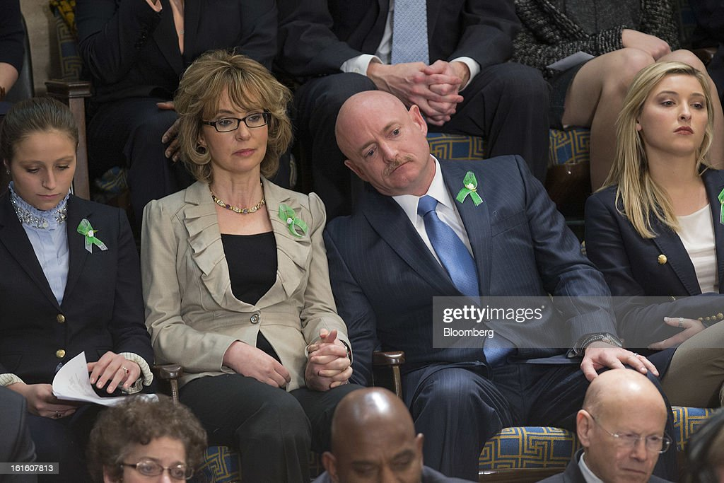 Former Representative Gabrielle Giffords, second left, and husband Mark Kelly, retired space shuttle commander, listen to U.S. President Barack Obama, unseen, deliver the State of the Union address to a joint session of Congress at the Capitol in Washington, D.C., U.S., on Tuesday, Feb. 12, 2013. Obama called for raising the federal minimum wage to $9 an hour and warned he'll use executive powers to get his way on issues from climate change to manufacturing if Congress doesn't act, laying out an assertive second-term agenda sure to provoke Republicans. Photographer: Andrew Harrer/Bloomberg via Getty Images