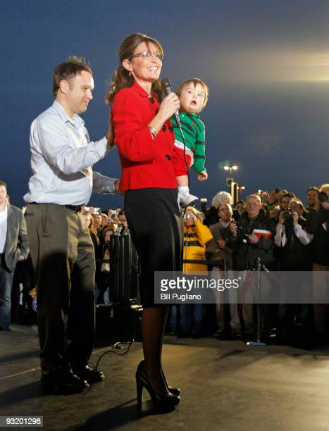 Former Republican vice presidential candidate and Alaska Governor Sarah Palin holds one of her children as arrives for a book signing event for her...