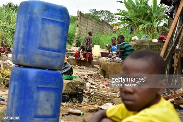 Former residents of a shanty town in Abidjan sit amongst the remains of their homes on May 26 2017 in Abidjan on the site of the death of 5...