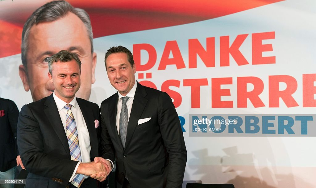 Former right-wing Austrian Freedom Party (FPOe) presidential candidate Norbert Hofer (L) and party leader Heinz Christian Strache (L) shake hands as they leave a news conference in Vienna, Austria, on May 24, 2016. Hofer the previous day was narrowly defeated by Austrian President-elect Alexander Van der Bellen, who had won the presidential elections run-off over Hofer by just a few thousands of votes. / AFP / JOE