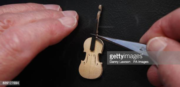 Former Royal Philharmonic Orchestra Cellist David Edwards sizes up a finger board against pieces of a miniature violin formed from Pearwood at his...