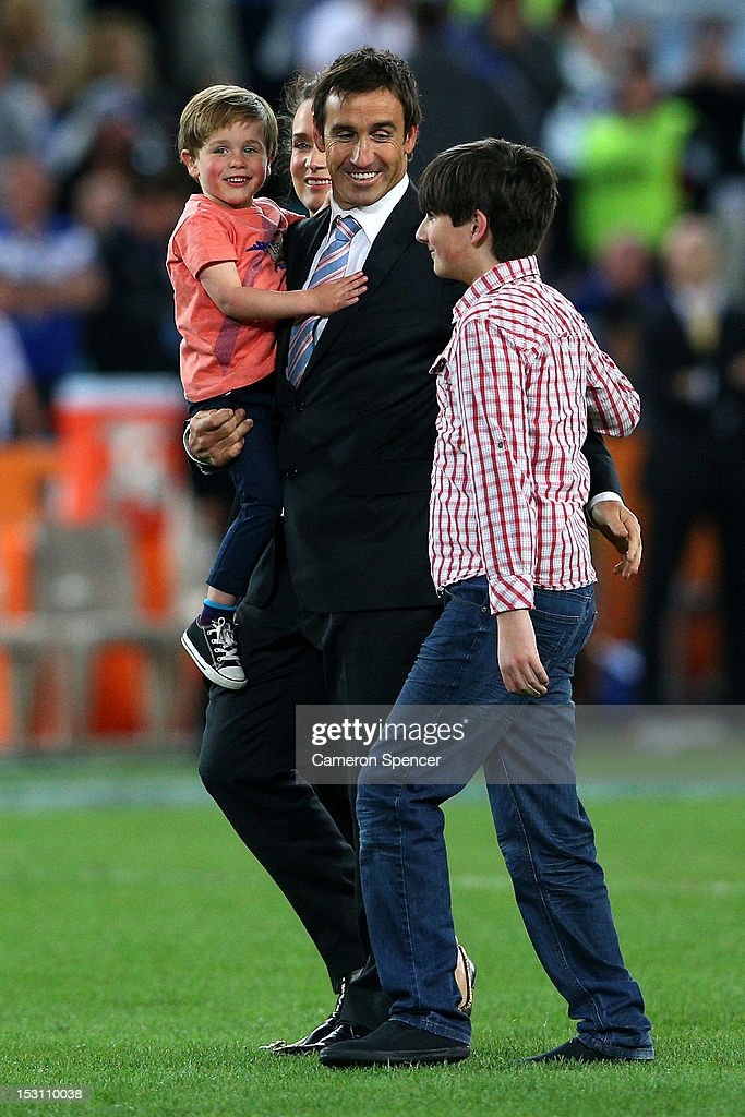 Former rugby league player Andrew Johns embraces his wife Cathrine Mahoney and his two son's Louis Byron and Samuel at half-time during the 2012 NRL Grand Final match between the Melbourne Storm and the Canterbury Bulldogs at ANZ Stadium on September 30, 2012 in Sydney, Australia. Andrew 'Joey' Johns has been named rugby league's eighth Immortal.