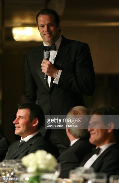 Former rugby player Martin Bayfield speaks as he stands behind Joe Calzaghe CEO Gordon Taylor and England manager Fabio Capello at the PFA Player of...