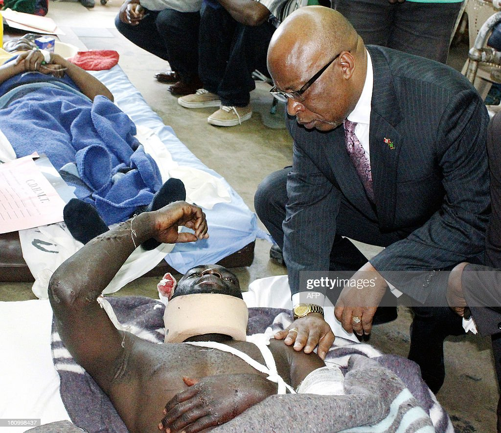 Former ruling party Movement for Multiparty Democracy (MMD) president Nevers Mumba talks to accident survivor 22-year-old McFarrin Bwalya at the University Teaching Hospital in Lusaka on February 8, 2013. Fifty three people were killed in a high-speed collision between a bus and a truck in Zambia on Thursday, the government said, one of the country's worst-ever traffic accidents.