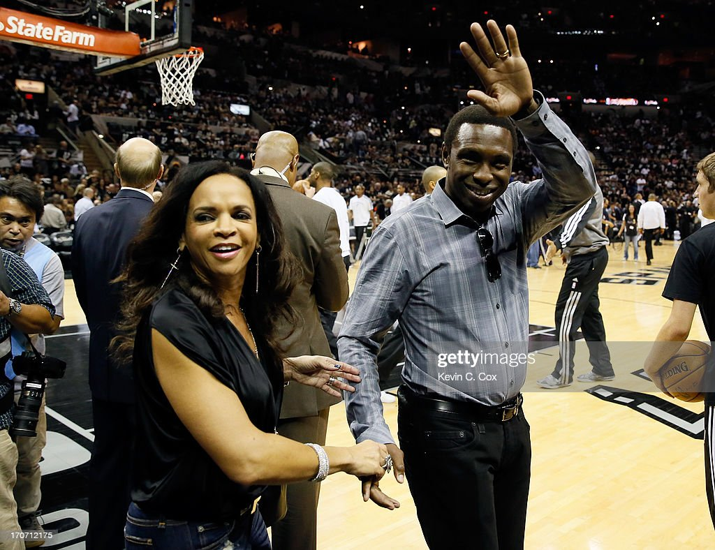 Former San Antonio Spurs player and coach Avery Johnson and wife Cassandra Johnson wave from the court before the Spurs take on the Miami Heat in...