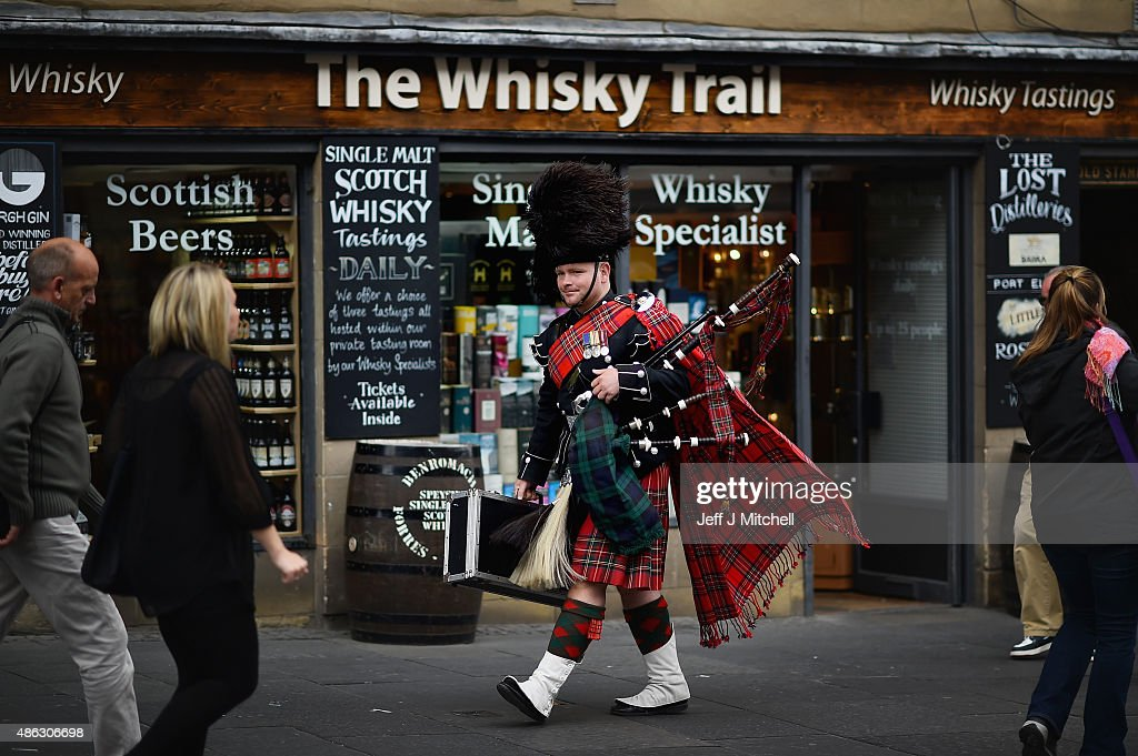 Former Scots Guards Piper David Barnet, walks past a whisky shop on the Royal Mile on September 3, 2015 in Edinburgh,Scotland. Plans to introduce a minimum unit price for alcohol in Scotland risk infringing EU rules on free trade, according to an initial ruling by Europe's top court.