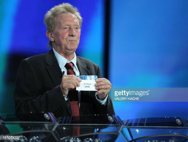 Former Scottish football player Denis Law displays a leaflet showing the name of Portuguese team 'FC Porto' as he proceeds to the draw for the UEFA...