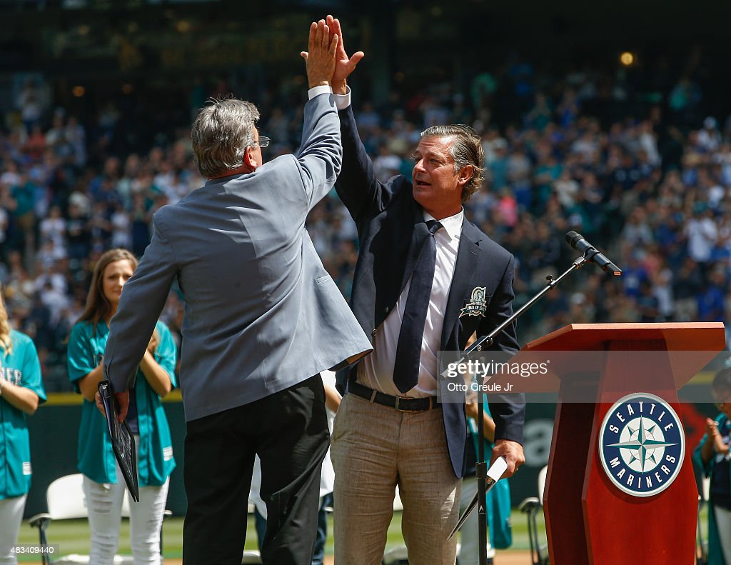 Former Seattle Mariners pitcher Jamie Moyer (R) gets a high-five from Mariners broadcaster Rick Rizzs during ceremonies inducting him into the Seattle Mariners' Hall of Fame prior to the game against the Texas Rangers at Safeco Field on August 8, 2015 in Seattle, Washington.
