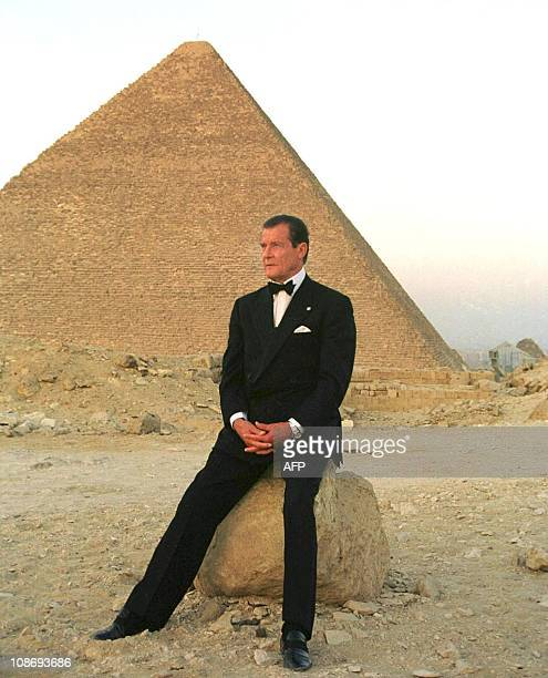 Former secret agent 007 Roger Moore poses in front of Cheops the largest of Egypt's three Pyramids on the Giza plateau south of Cairo 2 July 1999...