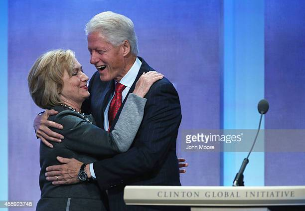 Former Secretary of State Hillary Clinton and former US President Bill Clinton embrace at the opening plenary session of the Clinton Global...