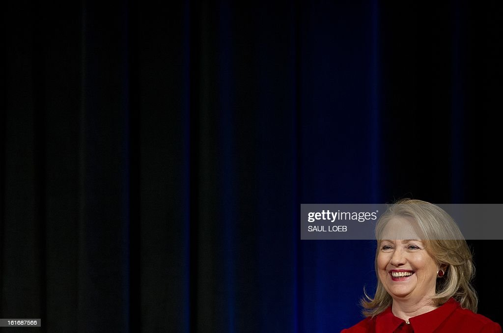 Former Secretary of State Hillary Clinton laughs as Secretary of Defense Leon Panetta jokes prior to Clinton receiving the Department of Defense Medal for Distinguished Public Service during a ceremony at the Pentagon in Washington, DC, February 14, 2013. AFP PHOTO / Saul LOEB