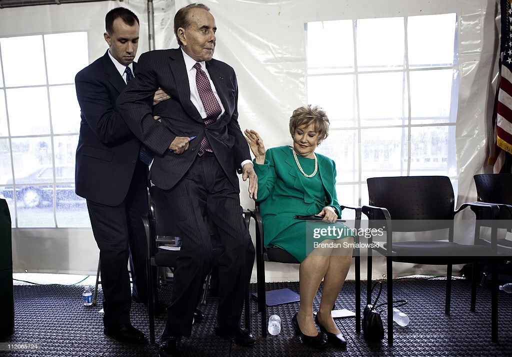 Former Senator Elizabeth Dole (R-NC) looks at her husband former Senator Bob Dole (R-KS) as he is helped to his feet during an event at the World War II Memorial April 12, 2011 in Washington, DC. Vice President Joseph Biden was joined by Secretary of the Interior Kenneth Salazar and others to dedicate a plaque for Dole's, a World War II veteran, involvement in building the memorial.