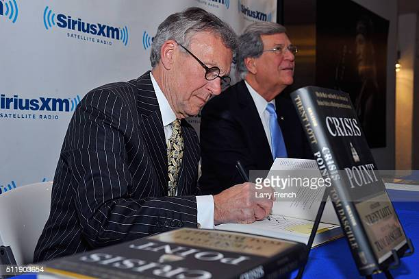 Former senators Tom Daschle left and Trent Lott right sign their new book Crisis Point at SiriusXMBipartisan Policy Center's event hosted by POTUS...