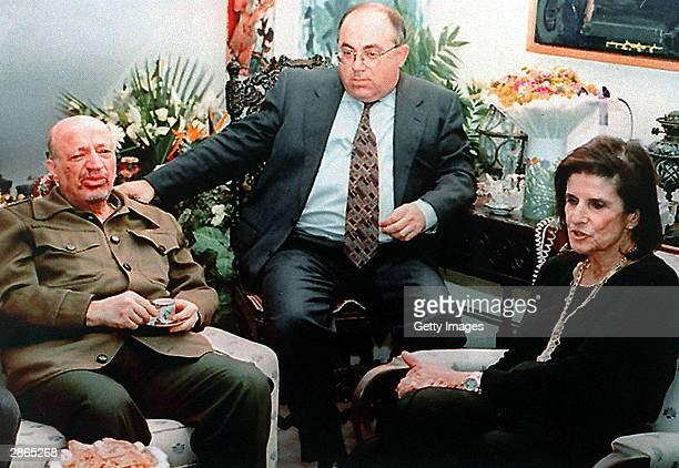 Former senior Shin Bet official Yossi Ginossar sits with a bareheaded Palestinian leader Yasser Arafat November 9 1995 during a condolence visit to...