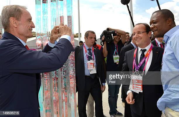 Former skier JeanClaude Killy takes a picture of French President Francois Hollande and a guest during a trip to the Olympic village on Day 3 of the...