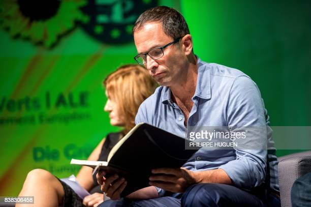Former socialist presidential candidate now leader of the 'mouvement du 1er juillet' Benoit Hamon reads as he attends a Europe Ecologie Les Verts...