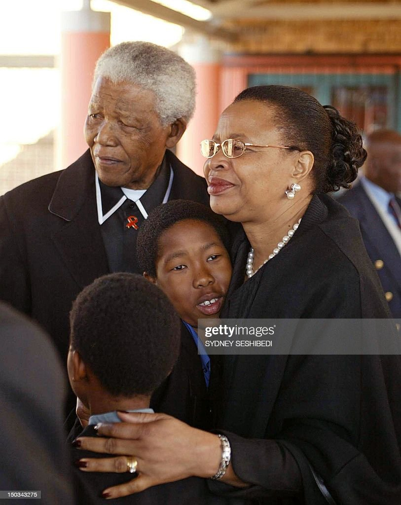 Former South African President Nelson Mandela (L) and his wife, Graca Machel, attend the funeral of Mandela's daughter in-law Joyce Zondi-Mandela who died of pneumonia and was buried at the community centre in Diepkloof Soweto, 20 kilometres south of Johannesburg, 19 July 2003. Zondi was married to Mandelas only remaining son Makgatho Mandela, from his first marriage to Evelyn Ntoko. The Mandela's hug her children.