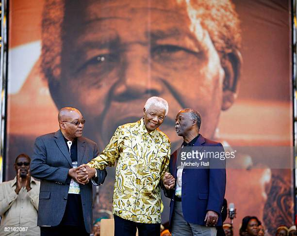 Former South African President Nelson Mandela flanked by President Thabo Mbeki and ANC President Jacob Zuma embrace hands at the ANC Madiba 90th...