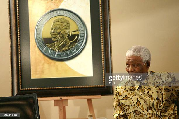 Former South African president Nelson Mandela sits near an image of a new Rand 5 coin issued to celebrate his birthday on July 7 2008 in Johannesburg...