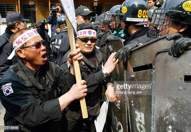 Former South Korean intelligent agents scuffle with riot policemen as they try to enter the Japanese Embassy during a rally against Japan's...