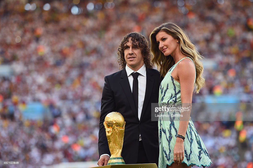 Former Spanish international <a gi-track='captionPersonalityLinkClicked' href=/galleries/search?phrase=Carles+Puyol&family=editorial&specificpeople=211383 ng-click='$event.stopPropagation()'>Carles Puyol</a> and model <a gi-track='captionPersonalityLinkClicked' href=/galleries/search?phrase=Gisele+Bundchen&family=editorial&specificpeople=201815 ng-click='$event.stopPropagation()'>Gisele Bundchen</a> present the World Cup trophy prior to the 2014 FIFA World Cup Brazil Final match between Germany and Argentina at Maracana on July 13, 2014 in Rio de Janeiro, Brazil.