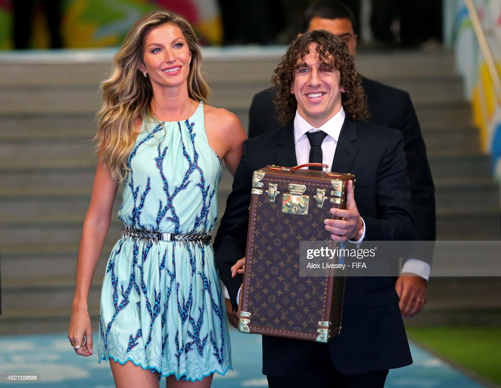 Former Spanish international Carles Puyol (R) and model Gisele Bundchen (L) walk in the tunnel to present the World Cup in a Louis Vuitton travel case prior to the 2014 FIFA World Cup Brazil Final match between Germany and Argentina at Maracana on July 13, 2014 in Rio de Janeiro, Brazil.