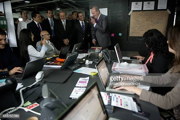 Former Spanish King Juan Carlos I of Spain tours a Spanish company in Bogota on August 6 2014 in the framework of his visit to Colombia for the...