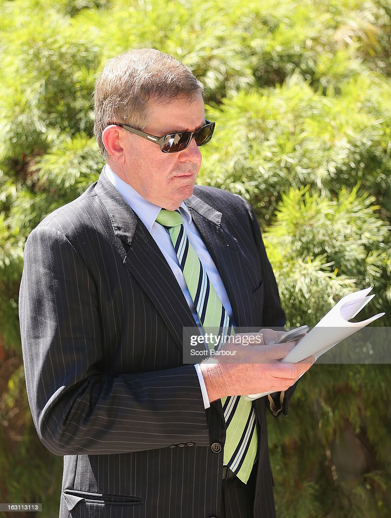 Former Speaker, Peter Slipper uses his mobile phone as he leaves the State Funeral for former speaker Joan Child on March 5, 2013 in Melbourne, Australia. Joan Child, the first female speaker of federal parliament passed away on February 23 at the age of 91.