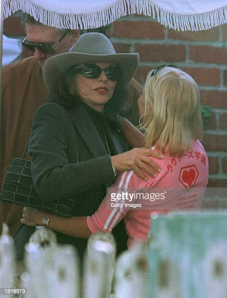 Former Spice Girl Geri Halliwell and actress Joan Collins hug each other goodbye before leaving the Ivy resturant January 18 2000 in Beverly Hills CA