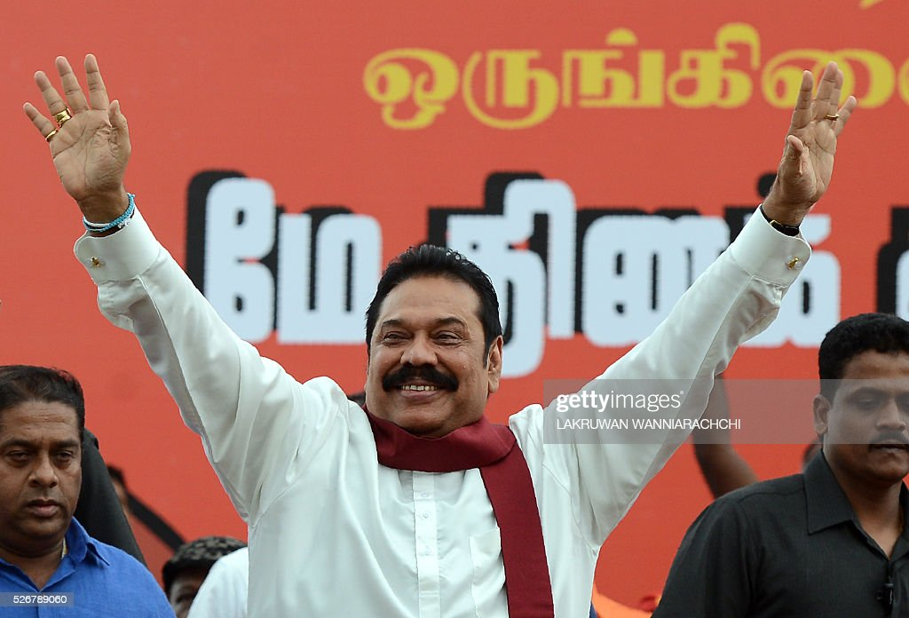 Former Sri Lankan president Mahinda Rajapakse waves as he arrives at an anti-government May Day rally in Colombo on May 1, 2016. Former President Mahinda Rajapakse who leads a faction of his successor Maithripala Sirisenas Freedom Alliance staged a rival rally to demonstrate his popularity despite being defeated twice in January and August of last year. / AFP / LAKRUWAN