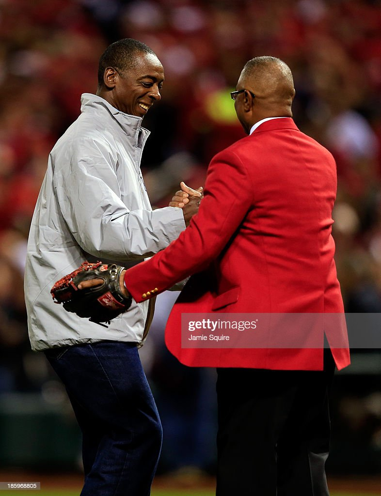 Former St. Louis Cardinals Willie McGee and Ozzie Smith shake hands as McGee throws out the ceremonial first pitch prior to Game Three of the 2013 World Series against the Boston Red Sox at Busch Stadium on October 26, 2013 in St Louis, Missouri.