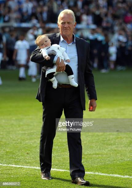 Former Swansea player Alan Curtis with one of his grandchildren on the pitch after the Premier League match between Swansea City and West Bromwich...