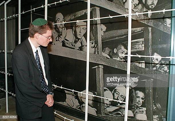 Former Swiss bank employee Christoph Meili looks 16 September at a picture showing Jewish detainees at the Buchenwald nazi concentration camp during...
