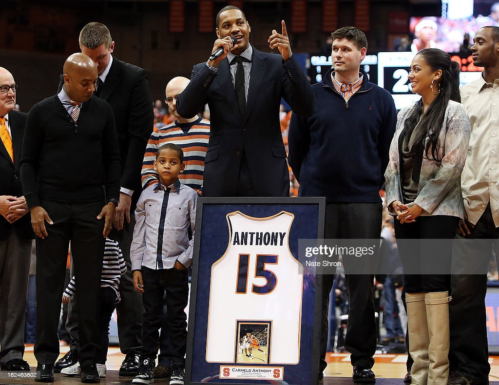 Former Syracuse Orange player Carmelo Anthony (C) speaks on stage next to athletic director Daryl Gross, son Kiyan Carmelo Anthony and wife Alani Vasquez along with members of the 2003 national champions team in a presenation retiring his jersey, #15 during half time in the game against the Georgetown Hoyas at the Carrier Dome on February 23, 2013 in Syracuse, New York.