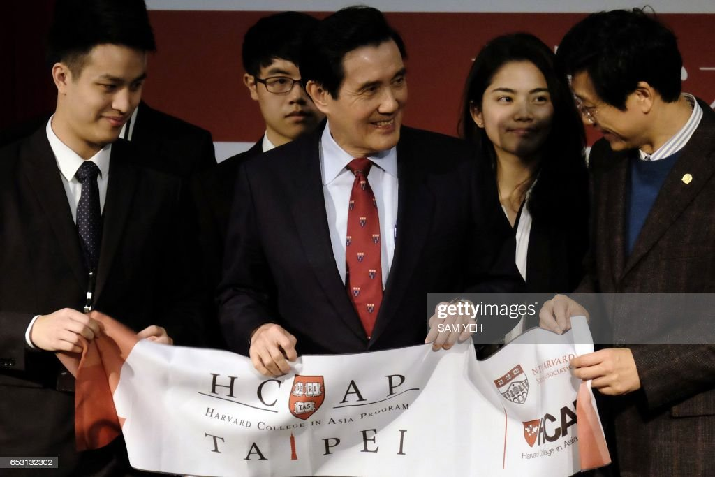 Former Taiwan president Ma Ying-jeou (C) displays a banner during a speech to the Harvard College Asia Program in Taipei on March 14, 2017. Taiwan's former president Ma Ying-jeou was slapped with new charges on March 14 in a political leaks controversy, just weeks before he faces possible conviction in another related case. / AFP PHOTO / Sam YEH