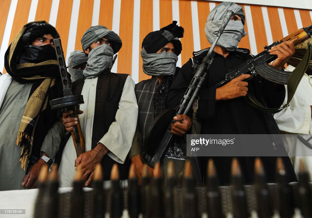 Former Taliban fighters stand with their weapons during a ceremony after joining Afghan government forces in Herat on August 7 2013 About 100000...