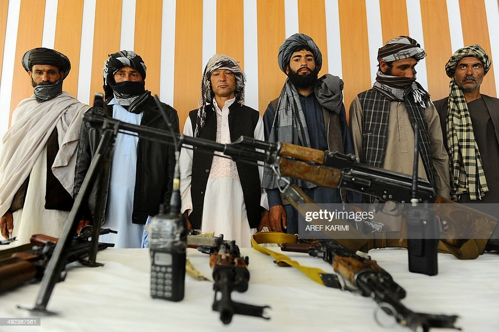 Former Taliban fighters stand with their weapons during a reconciliation process in Herat province on May 20 2014 A twenty onemember armed group of...