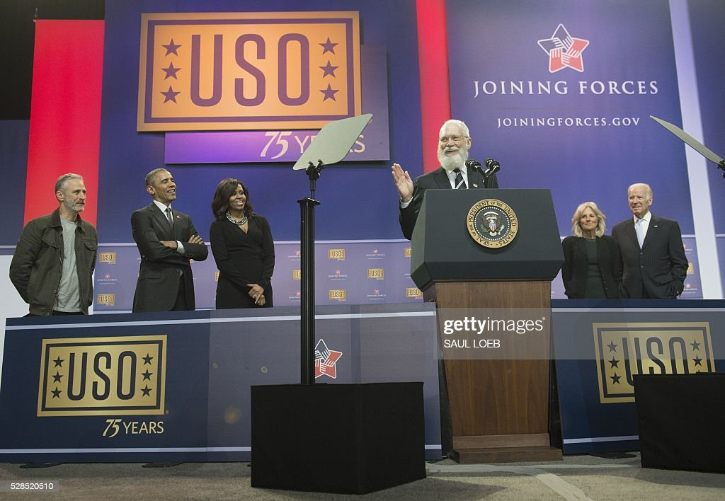 Former talk show host David Letterman speaks alongside (L-R) Comedian Jon Stewart, US President Barack Obama, First Lady Michelle Obama, US Vice President Joe Biden and his wife, Jill Biden, during a celebration of the 5th anniversary of Joining Forces and the 75th anniversary of the USO at Andrews Air Force Base in Maryland, May 5, 2016. / AFP / SAUL