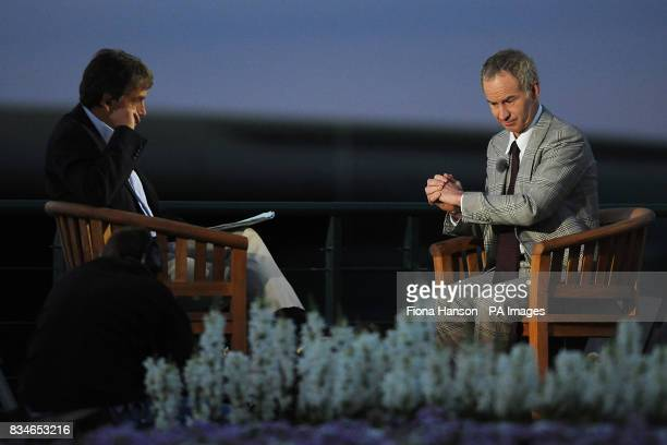 Former Tennis player John McEnroe chats with BBC presenter John Inverdale under studio lighting outside as dusk falls at Wimbledon